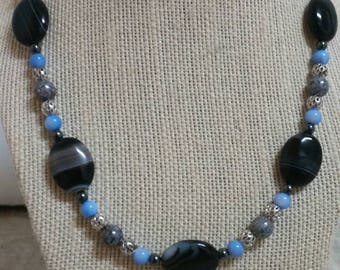 Exquisite, 20 inch necklace featuring banded onyx ovals, light blue shell, Czech gray luster beads, hematite, and inlaid metal beads