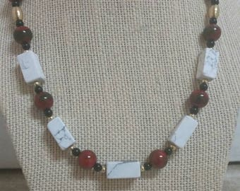 Striking, 19 inch necklace featuring white howlite rectangles, dark red acrylic beads, black jasper beads, brass beads, hair pipe tubes