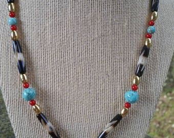 Native-inspired, and eye-catching 20 inch necklace featuring turquoise howlite, red bamboo coral, brass beads, and buffalo horn tubes