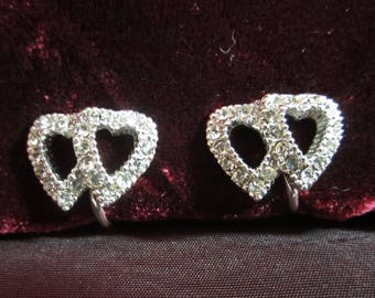 Vintage 1960's Doulbe Heart Shaped Rhinestone Screwback Earrings on Silvertone Mounting.  Good Condition.  Small Scale