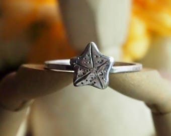 A wonderfully simple handmade and unique fine silver starfish on a square sterling silver ring.