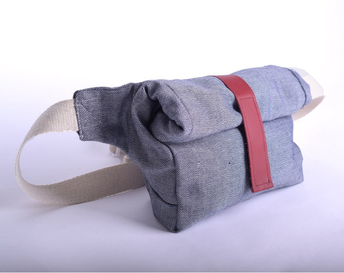 Minimalist roll top hip bag or shoulder bag in light denim with up-cycled leather strap