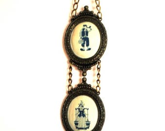 Vintage 50s,   two oval miniatures  with  ornate metal frame and  and blue and gray cross stitching a  dutch figures of the men and women.