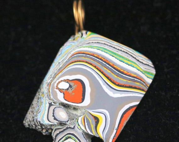"Fordite pendant, orange gray white yellow green, ""Dark Blue Eye"", brass twirl bail 26.5ct"