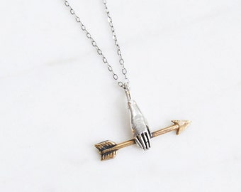 Hand with golden arrow necklace