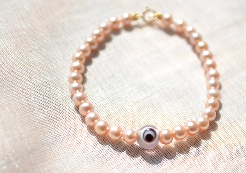 Baby Freshwater Pearl Bracelet with pink evil eye charm image 0