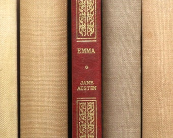Emma by Jane Austen bound in faux red leather with gilt decoration.