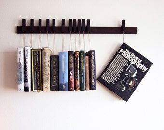 Custom made wooden book rack / bookshelf in dark wood. Pins also work as bookmarks. Bookcase