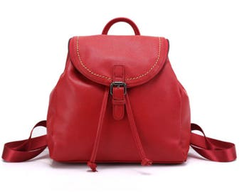 Red leather drawstring flap backpack with contrast stitching and zipper decor