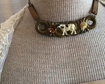 Repurposed drawer hardware choker with leather detail . Farm themed with cow centerpiece . Boho chic