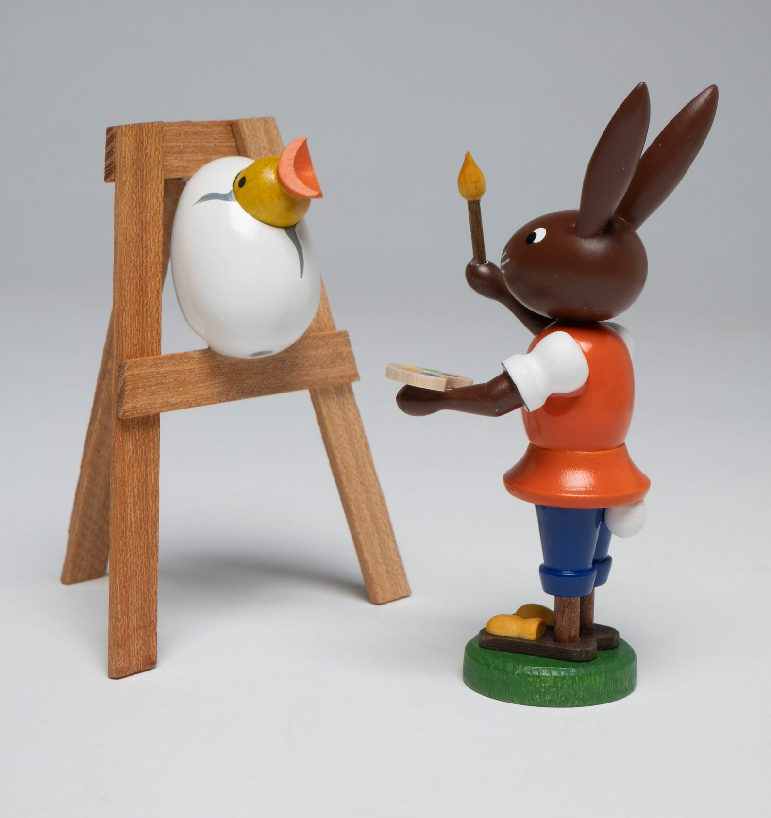 Erzgebirge Handarbell Bunny artist painting a yellow chick in egg on easel Erzgebirge folk art hand painted made in Germany