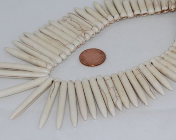 A strand of Graduated 45x5mm to 12x5mm Point Round Spike Creamy White Howlite.