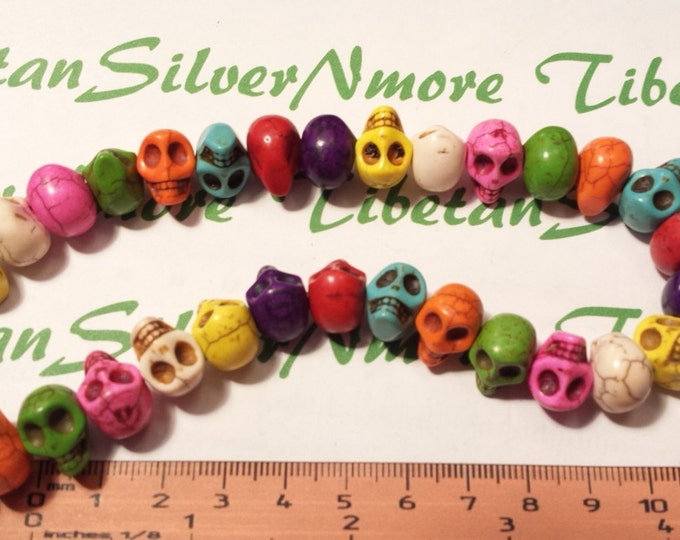 A strand of 38 pieces of 14x10mm 3D Skulls side to side drilled Multi-color Dyed Magnesite.
