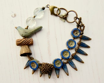 Birds of a feather - handmade artisan bead bird and branch bracelet in blue, brown and bronze - Songbead, UK, narrative jewellery
