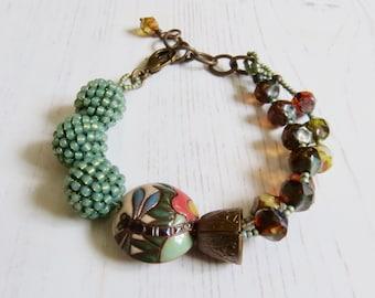 Handmade artisan bead bracelet - Anisoptera - artisan bead bracelet in red amber green with dragonfly - Songbead, UK, narrative jewelry
