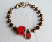 Handmade artisan ceramic and glass bead bracelet in red and bronze with house and ladybird beads - songbead, eclectic colourful jewellery