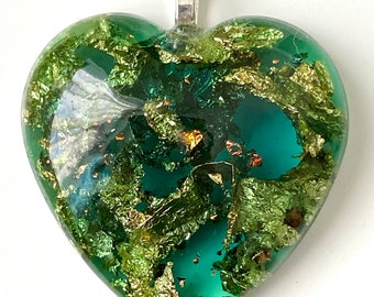 Transparent teal green heart-shaped domed resin pendant, encapsulating gold and copper leaf detail with a wide silver heart bail