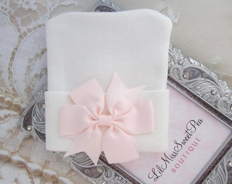White Newborn Hospital Hat with a light pink pinwheel ribbon pearl bow, baby hat, perfect baby shower gift, from Lil Miss Sweet Pea Boutique