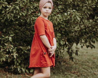 Girls pocket knit dress in rust.    Available girls 12 months  to 12 years.