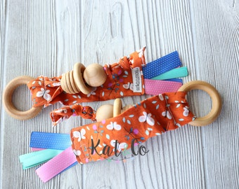 Natural maple teething ring in organic orange butterfly fabric.  Can be personalized.