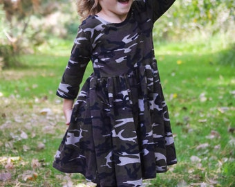Girls 3/4 sleeve camo camouflage dress.   Fitted bodice with scoop neck and full skirt.   Available girls 6 months to 12 years.