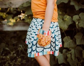 Girls kitty skirt with pocket.  Elastic waist, super full.  Custom made sizes 12 months to 12 years.