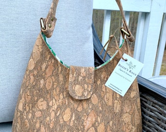 Textured cork sling purse with green leaf liner fabric.