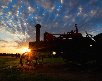 Photograph of an Antique Tractor in a Field Against a Brilliant Sunset in the Country