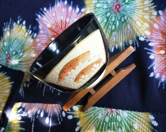 Vintage Japanese hand-made Kyoware glazed tea bowl, chawan . Painted on-glaze enamel spring and autumn, black glaze,  white porcelain body.