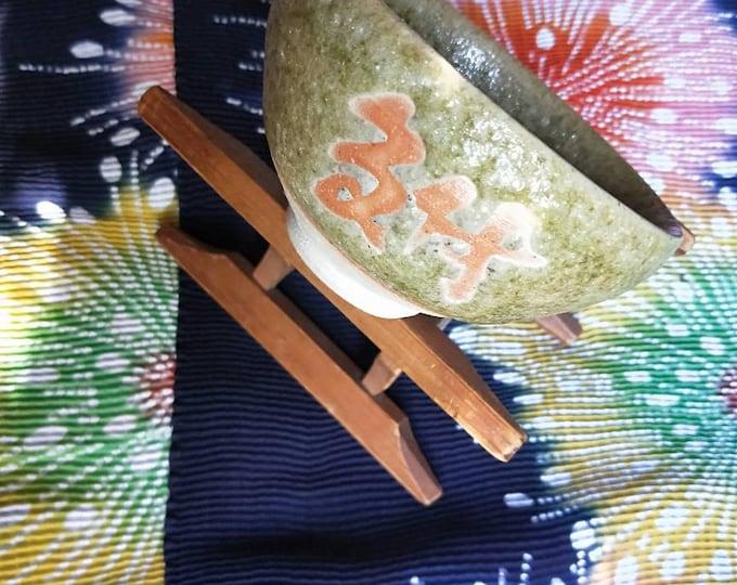 Vintage Japanese hand-made stoneware glazed tea bowl, chawan .Calligraphy, green textured glaze with pink slip.  White stoneware body.