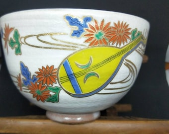 Vintage Japanese hand-made tea bowl. Kyo-ware, brown stoneware, with cream glaze and on-glaze paint Shamisen and chrysanthemum