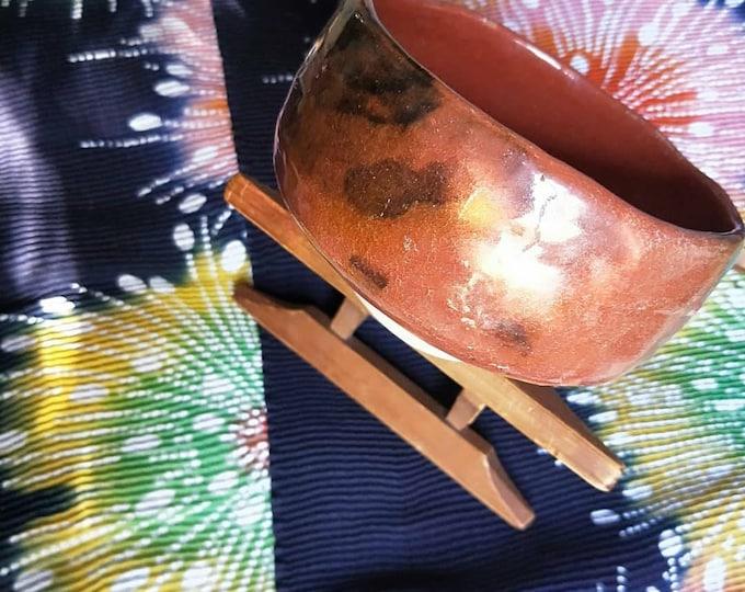Vintage Japanese hand-made raku ware glazed tea bowl, chawan . Red glaze earthenware body.