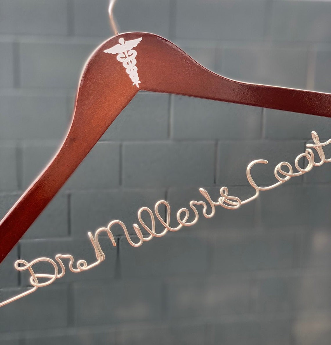 image of coat hanger with the horizontal part being wire bent into the shape of a doctor's name.