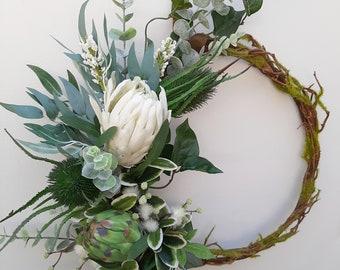 Green and white wreath.  Protea, thistle, eucalyptus.  Australian christmas wreath, door decoration. Mossy vine wreath.