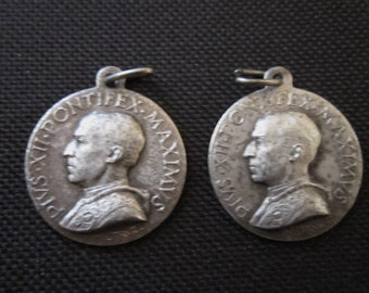 Two Pope Pius XII religious medallions with Holy Family on back, early 1940s, signed Mestruzzi