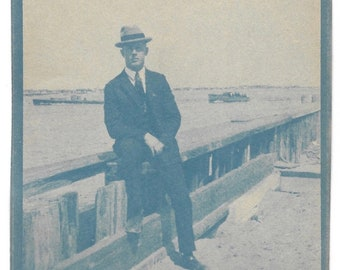 Vintage Cyanotype Photo Handsome Young Man Sitting On Pier Classic Wooden Speedboats In Background Vintage Cyan-Blue Print