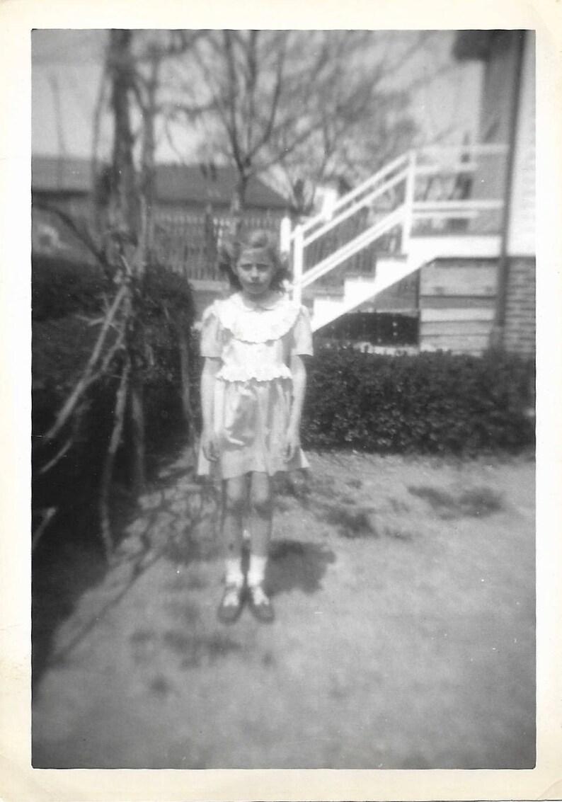 Peculiar child stiff pose unusual black white snapshot photo
