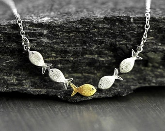 Swimming against the current. Dainty silver necklace. School of fish with one golden enameled fish swimming upstream. Gift for her.