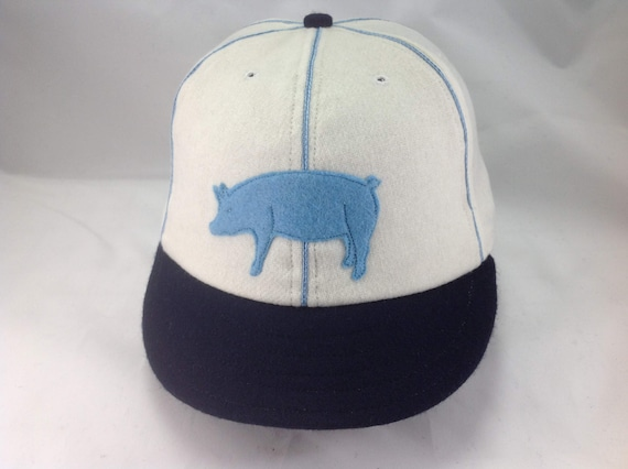 "Hog-n-Hominy Vintage Base Ball team cap. White wool cap and  navy 2"" visor and button. Baby blue hog and soutache. Select size at checkout"