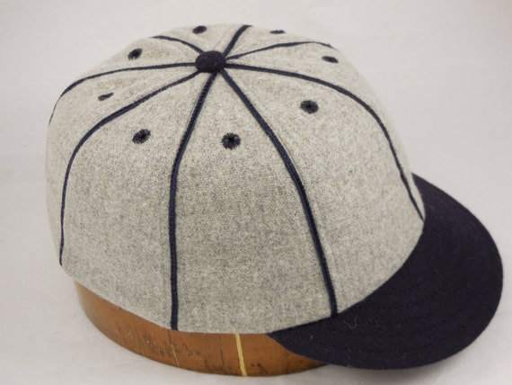 Light grey melton wool 8 panel baseball cap with navy soutache, eyelets, 2 inch visor, shallow vintage cut, supple leather sweatband, fitted