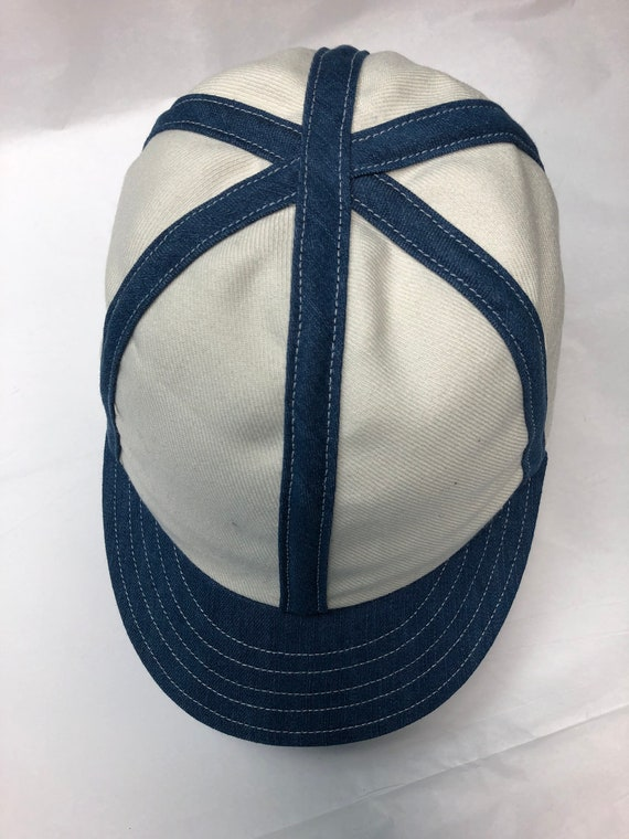 Off white acrylic wool serge 6 panel cap with contrasting denim exterior binding and visor. Fitted to any size.