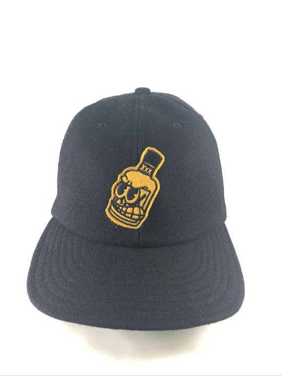 Whiskey Bottle - By Russell Balliet - Black melton wool 6 panel cap with flexible visor and wool felt embroidered patch. Any size available.