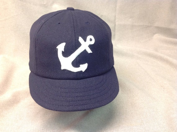 Navy melton cap with wool felt anchor logo. Fitted or adjustable available.
