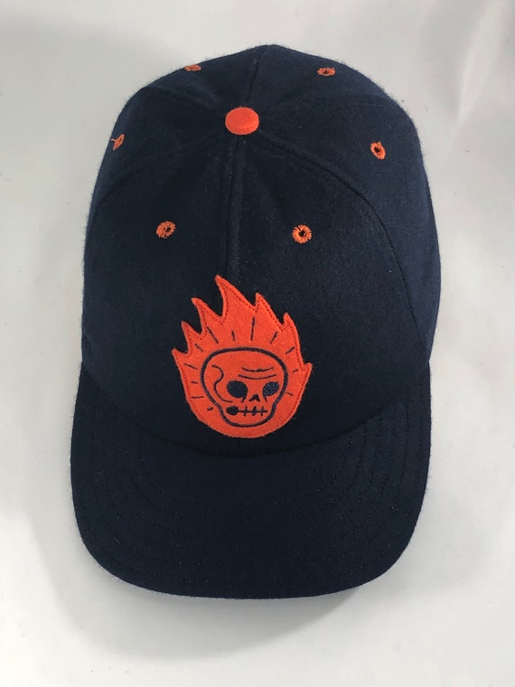 """Flaming skull felt patch, art by Ryan Hungerford. Navy melton wool cap 6 panel with 2.5"""" visor. Any size available."""