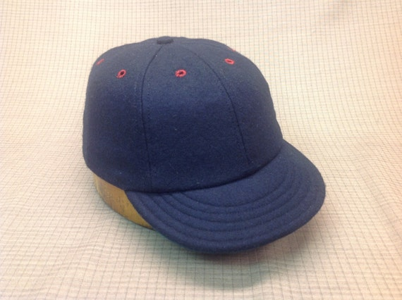 Custom made navy wool cap with burgundy eyelets. Any size available, fitted or adjustable.