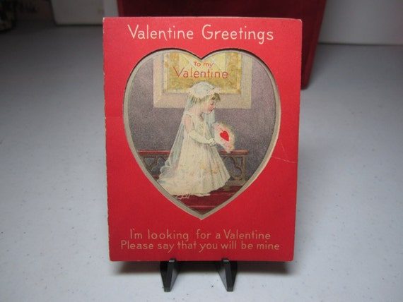 1920's-30's adorable die cut heart window valentine card shows little girl dressed in a bridal gown and veil holding a red heart bouquet