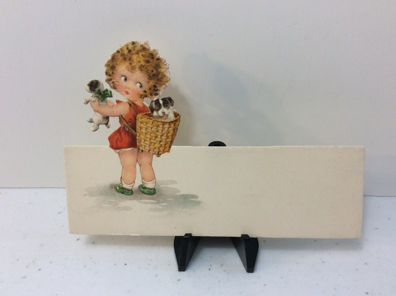 Adorable unused 1920/'s die cut Germany place card sweet little girl holds puppy looks over her shoulder at other puppy in basket on her back