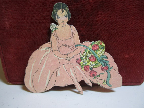 1920's-1930's die cut art deco place card pretty flapper girl in pink dress holding a basket of red roses unused
