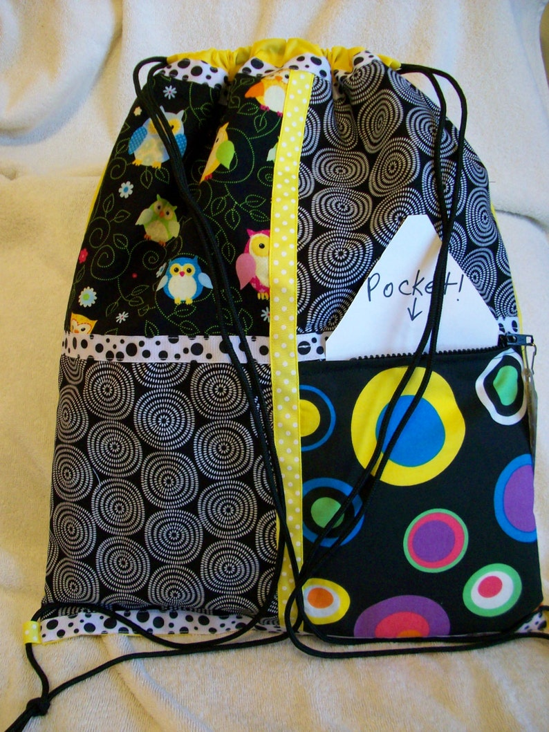 owls in brights with circles in colors and black and white on a yellow ripstop nylon drawstring backpack with front zipper pocket