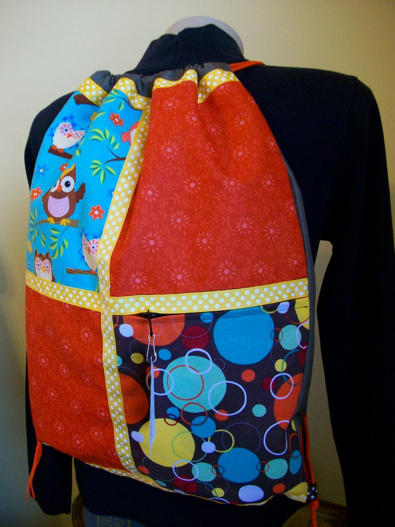 owls with orange and gold accents on a brown ripstop nylon drawstring backpack with front zipper pocket